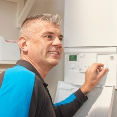 A smiling British Gas engineer conducts a business gas safety check on a commercial boiler