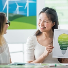 A smiling woman uses a graph to show the benefits of renewable energy plans for businesses