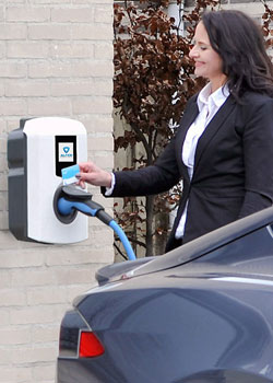 Business women raising charge card to wall charger – Business electric vehicle charging point installation