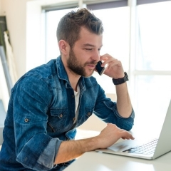 A bearded micro business owner sits at a desk while talking on a mobile phone