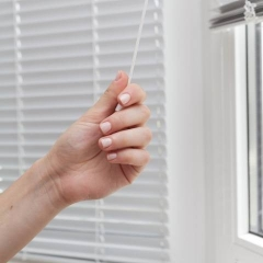 A hand pulling a string to open hotel blinds