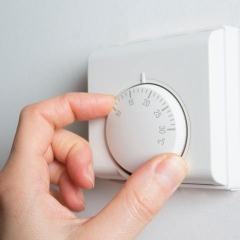 A hand turning down a heating thermostat