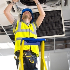 An engineer on a ladder works on a ceiling ventilation unit
