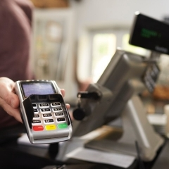 A cashier presents a card machine at a till