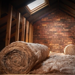 A roll of loft insulation in ceiling space underneath a roof light